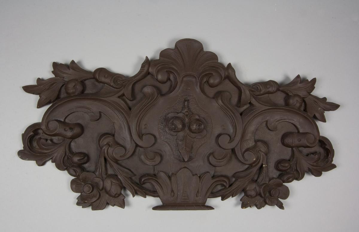 Ornament av brunmålat trä. Skuren växtornamentik. Slät baksida med två hylsor av metall för att fastsättning av ornamentet på okänt föremål.