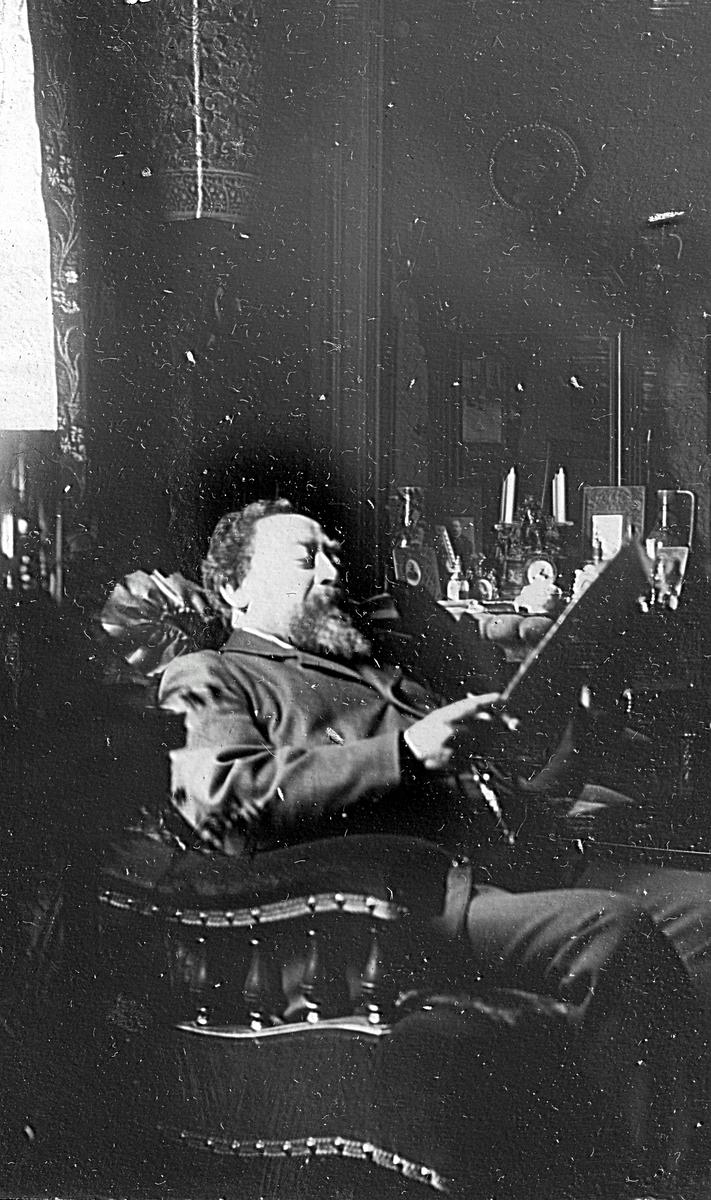 En man som sitter och läser. Fotograf Alfred Bergendahl. Givare H Bergendahl.