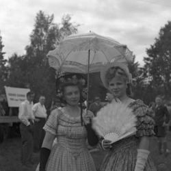 Foto av två kvinnor med utklädsel till möjligen maskerad? En