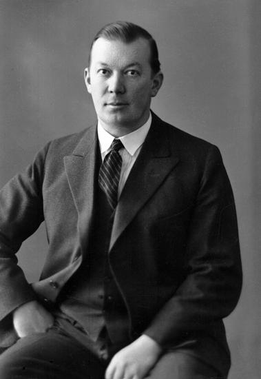 Foto av en okänd man i mörk kostym med väst och randig slips.Knäbild. Ateljéfoto.Trol. Ivar Reinhold Gustafsson (1893-1966), Ulvagraven, Blädinge.  Jfr MINI0978. Källa: Sveriges Dödbok 1901-2009.