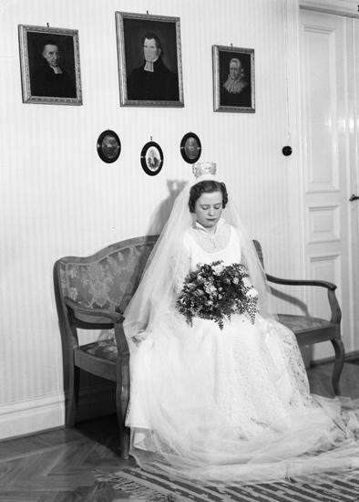 Foto av en brud i vit brudklänning, slöja och stor brudkrona.Hon sitter i en soffa i en sal.Helfigur.Stig Herman Pleijel (1924-2007), Alvesta (senare Tingsryd). Gift 29 december 1954 med   ?   .Källa: Sveriges Dödbok 1901-2009.