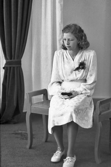 Foto av en ung kvinna i vit konfirmationsklänning. Hon sitter på en stoppad bänk och håller en liten psalmbok i händerna.Helfigur. Ateljéfoto.