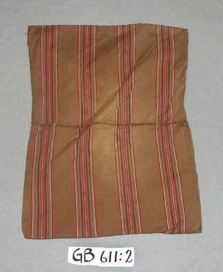 Kuddvar. Handvävt.  Kvalitet: bomull. Teknik: oliksidig kypert. Varp: brunt. Inslag: brun botten. Ränder i färgerna rött, vitt,  beige, brunt och blått. Mönsterrapport 12 cm bred. Två kuddvar hopsydda för hand.  Inskrivet i huvudkatalogen 1996-1997.