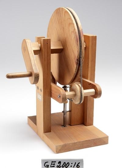 """Maskin-modellbygge i trä och metall , """"fysik-slöjd"""".  Denna modell var elevarbete efter deras fria val av mekanisk rörelse. Modellen var i tjänst inom olika slöjd och som undervisningsmaterial i linearritning.  Inskrivet i huvudbok 2008."""