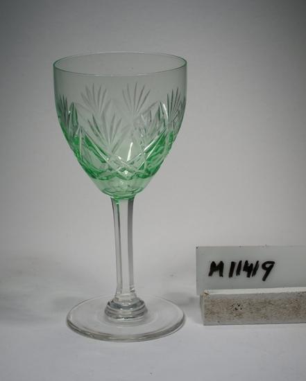Vitvins- eller cocktailglas. Ej identifierat. Se M 11404 - M 11425, samma servis. Skärslipad dekor. Facettben. Grön kuppa, ben och fot ofärgade. Klarglas. Ovan angivna mått avser övre diameter. Fotdiameter: 56 mm. Inskrivet i huvudkatalogen 1942. Funktion: Vitvins- eller cocktailglas