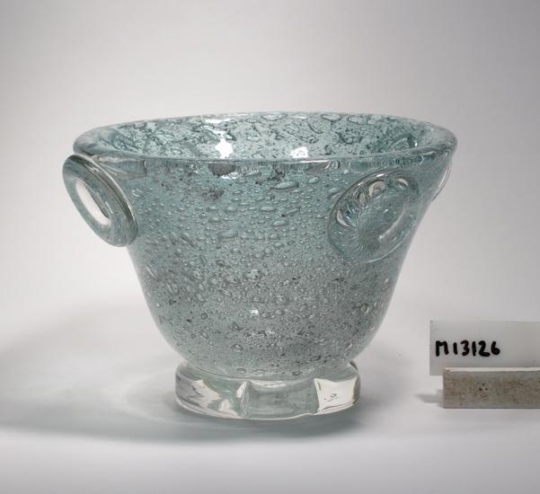 Skål med fot.  Formgiven av Willem H. G de Moor. Tillverkad 1940 enligt huvudkatalogen. Beskrivning: Glasmassa med blåsor. Stämplade påklipp (ser ut som ringar), fyra stycken, vid skålens övre kant. Färg: Blågråtonat, halvklart glas. Blåsigt. Mått: Ovan anges höjd och övre diameter (159,5 mm).  Bottenmått: 80 mm. Inskrivet i huvudkatalogen 1943. Funktion: Skål