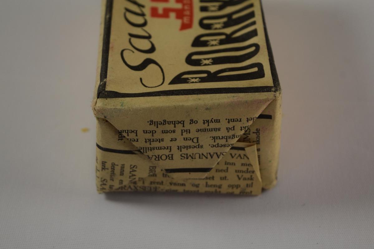 """Rektangulær såpe, brun, tre like såper (A, B, C) innpakket i papir med trykk. Produsert på Saanums Sepefabrikk i Mandal. Rektangulær fordypning med relieffteksten """"Borax"""" på overside og """"Saanum"""" på underside."""