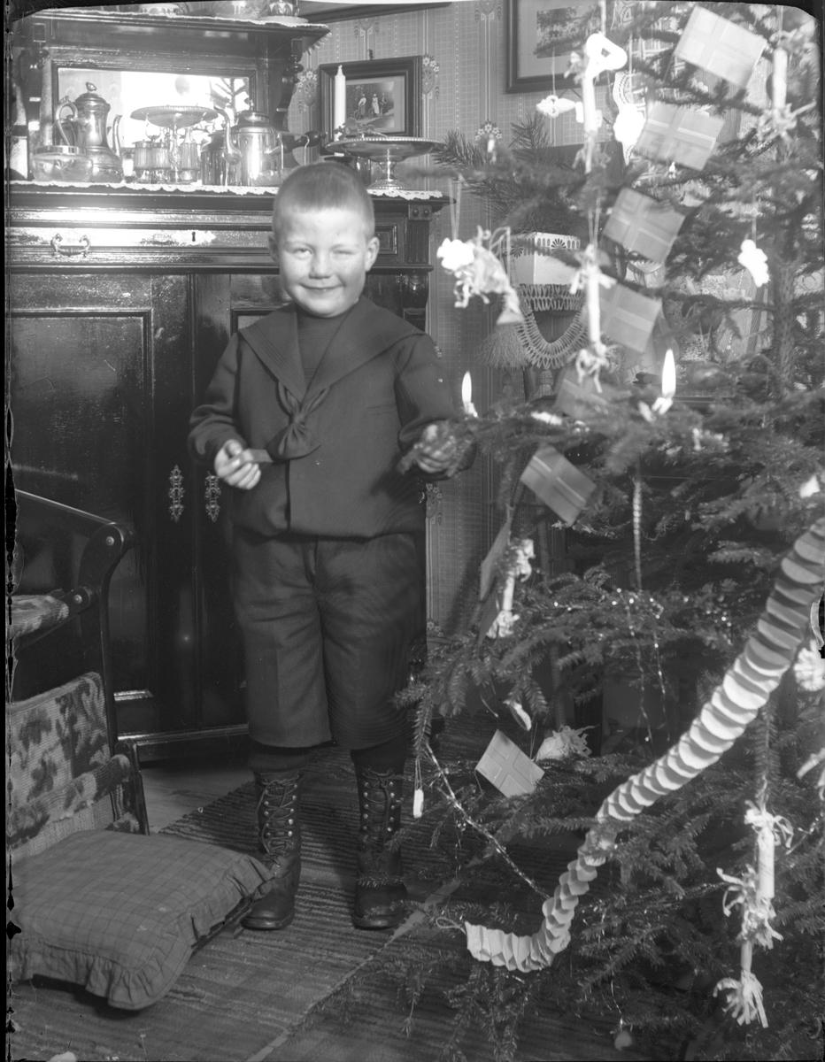 Pojke vid julgran.