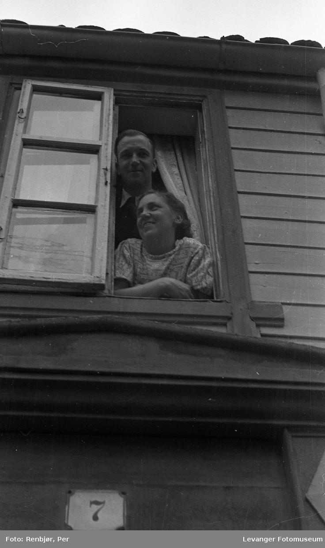 Speidernes opptog fredsvåren, et par titter ut av vinduet og ser på opptoget.