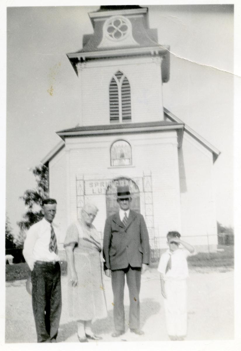 Springdale Lutheran Church i Wisconsin. En kvinne, to menn og en gutt står foran kirka. Mannen med dress og hatt er Olaus Islandsmoen.