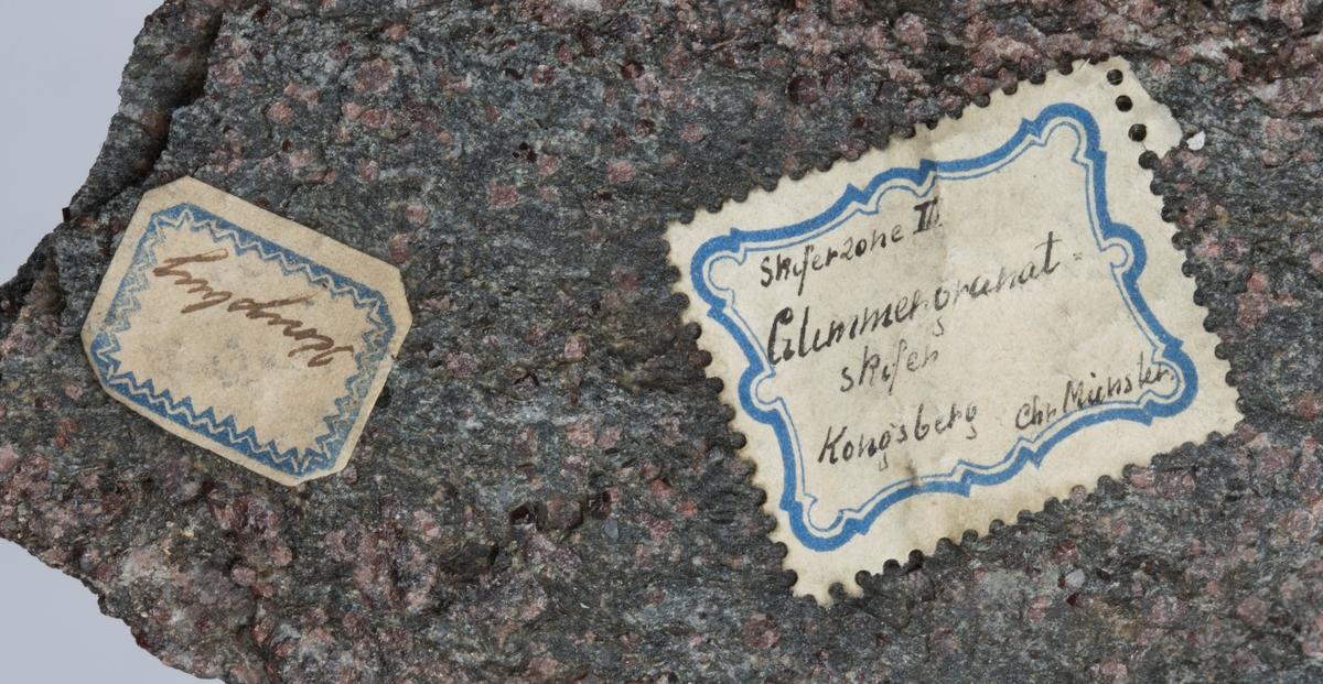 To etiketter på prøve:  Etikett 1: Kongsberg  Etikett 2: Skiferzone III Glimmergranat skifer Kongsberg Chr. Münster.