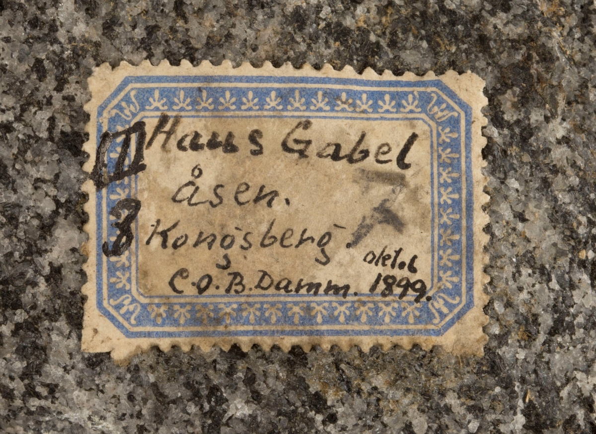 Etikett på prøve: III 3 Haus Gabel  åsen. Kongsberg. C.O.B. Damm oktob 1899.