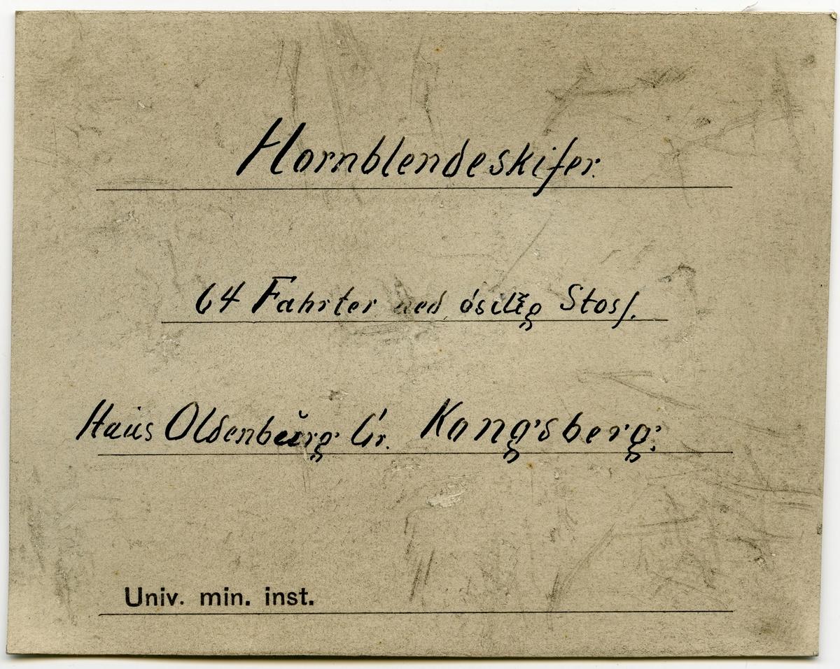 To etiketter i eske:  Etikett 1: Indlagte er fra 64 Fahrter i Østre Stoss.  Etikett 2: Hornblendeskifer. 64 Fahrter ned østlige Stoss. Haus Oldenburg Gr. Kongsberg.