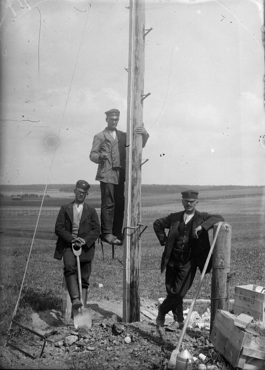 Tre män vid elstolpe, sannolikt Sävasta, Altuna socken, Uppland