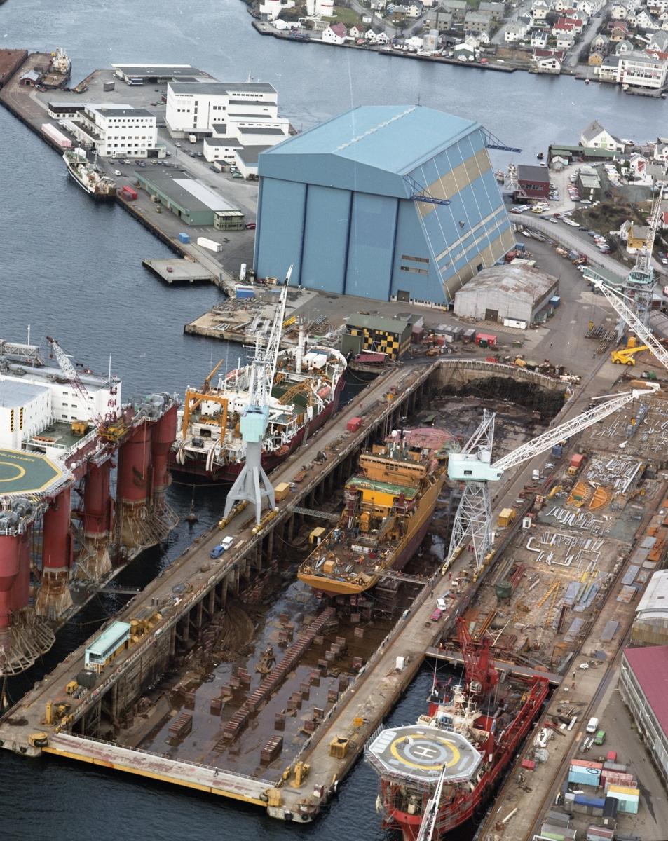 Flyfoto H.M.V. Oversiktsfoto. Skip og platformer ved kai.  Nordsjøhallen i bakgrunnen.