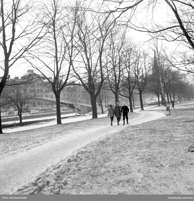 Vintervy från östra Norrmalm mot puckelbron. Tre barn på promenadvägen.