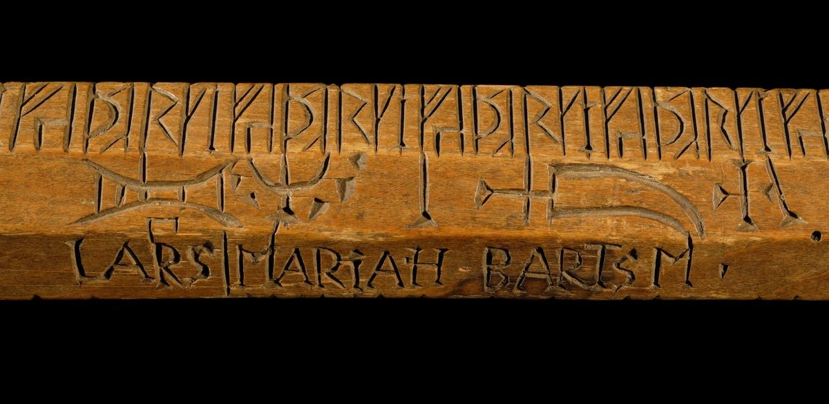 Kalenderstav i form av en stavformad runkalender. Av trä med åttkantigt genomsnitt och utmärkt väl skuren, Med latinska bokstäver texten: EN:R.J.M.K.J.Ä.P:E.L.E. R:K.J.E.J.A.R: Y.U.L.JD:K.A.L.E.N.D.A.R.J.U.M. ANNO 1702.