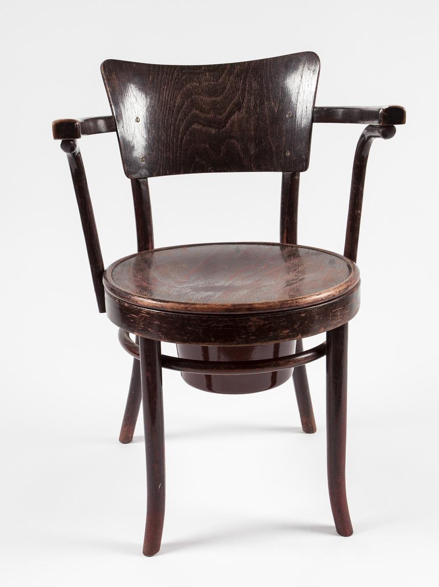 Toalettstol i fem deler. Stol, rundt sete, trering, metallbøtte med hank, metallokk. Stolen har buet ryggplate og armlener, bøtte og lokk av emaljert metall. Det er sølt hvit maling på armlenene.