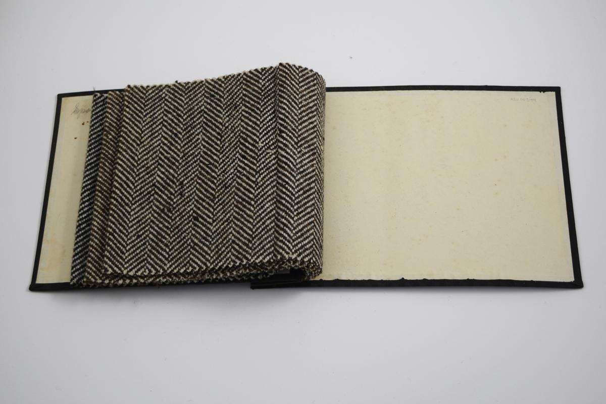 Prøvebok med 3 prøver. Middels tykke stoff med fiskebensmønster. Vevemønsteret er likt på alle stoffene, men fargene varierer. Stoffene ligger brettet dobbelt i boken. Stoffene er merket med en rund papirlapp, festet til stoffet med metallstifter, hvor navn og nummer er påført for hånd.   Stoff nr.: Sport/1, Sport/2, Sport/3.