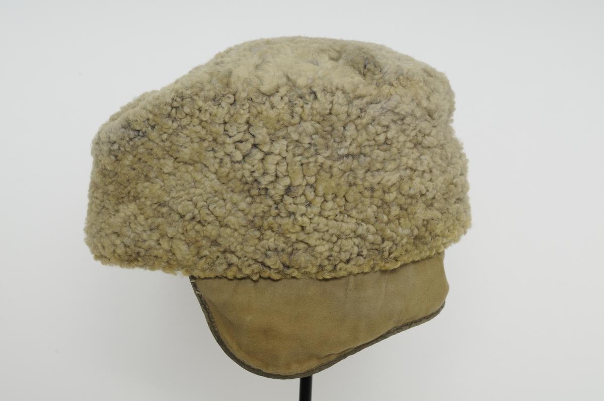 Grå saueskin lue med 11,5 cm høg kant.  Flat pull 17,5 cm i diameter. Oppbretta øyreklaffar på innsida. Fòra med svart bomullstøy.