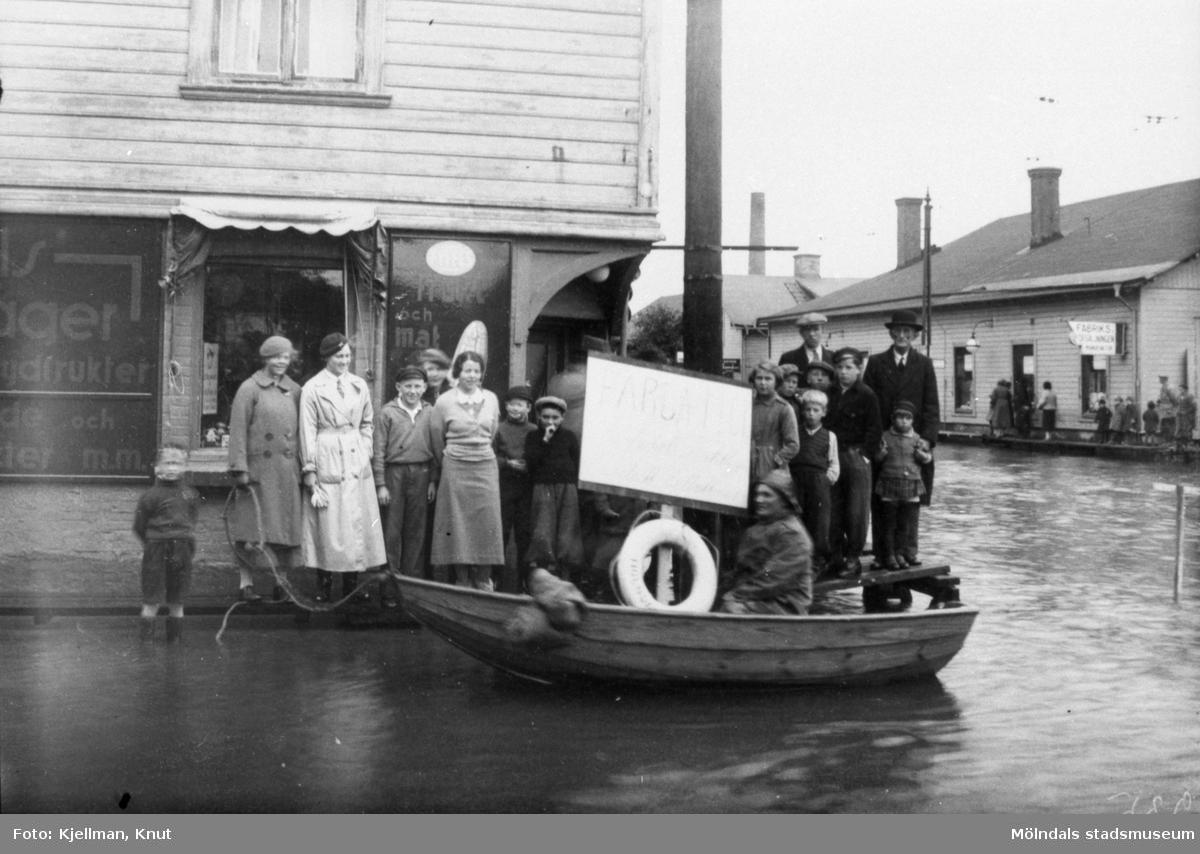 """Översvämning vid Mölndalsbro år 1935. Man ser en """"Färja"""", en roddbåt som förde folk över till Mölndals fruktlager. Till vänster ses Göteborgsvägen 1 och i bakgrunden spårvagnshallarna i hörnet mellan Kvarnbygatan och Göteborgsvägen."""