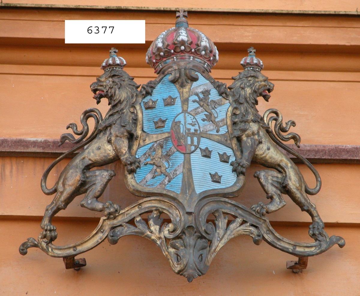 Akterstävsornament av metall. Föreställer Riksvapnet. Även försedd med kungl. krona (trasig). Har tillhört pansarbåten Oden.