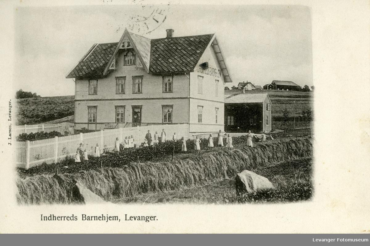 Postkort av barrnehjemmet på Levanger, barna foran bygningen i grønnsakfeltet.