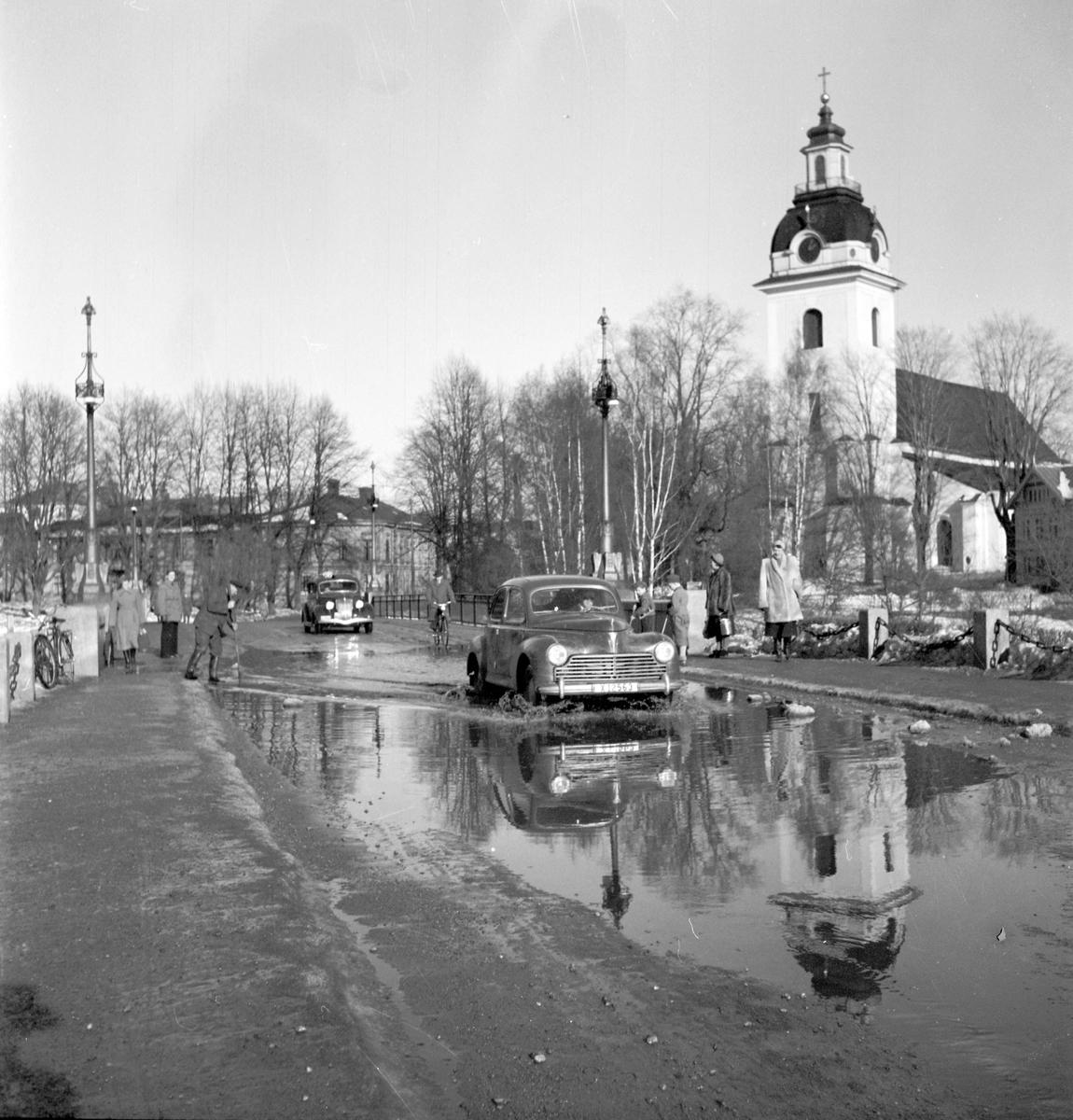 Vårreportage. Bil på Drottningbron, Heliga Trefaldighetskyrkan, översvämning. Den 3 mars 1950