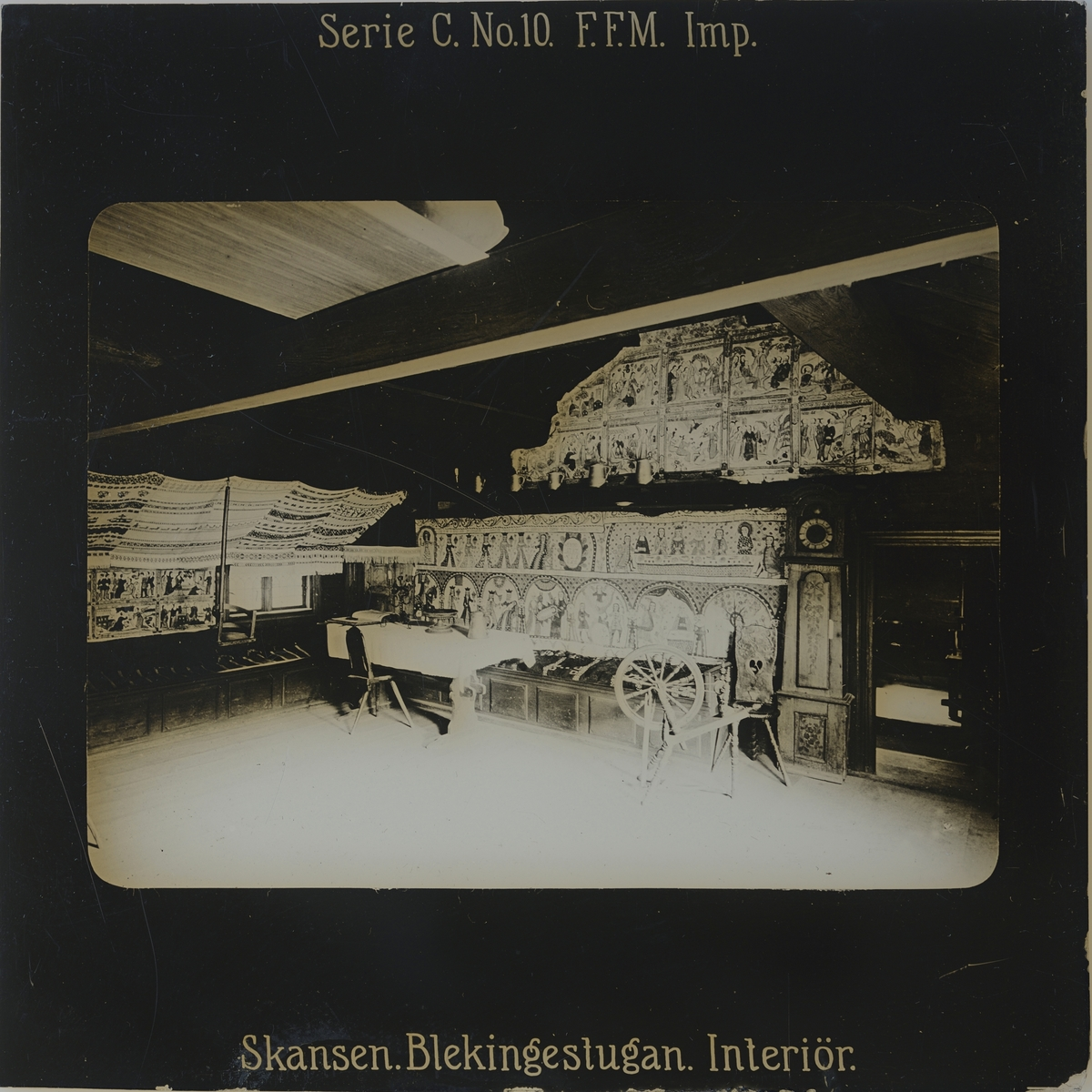 Interiör från Blekingestugan, även kallad Kyrkhultsstugan, på Skansen. På bilden syns målade och vävda bonader på väggarna, ett dukat bord, spinnrock, golvur m.m.