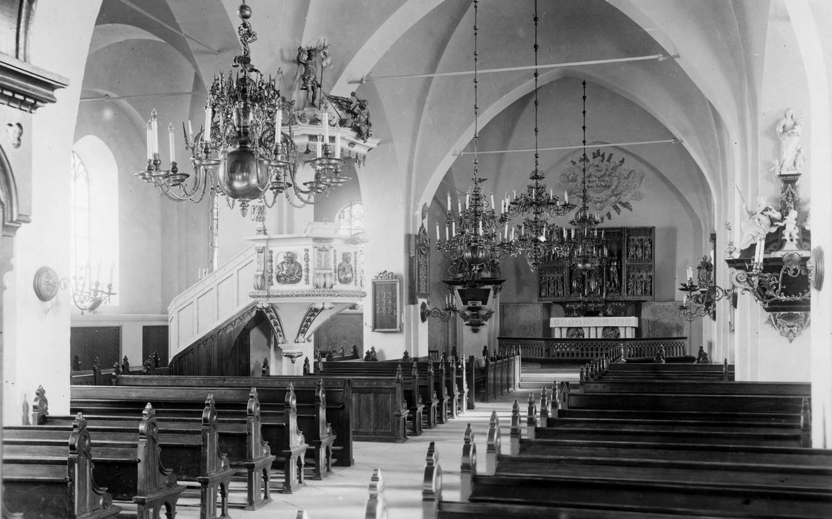 Kyrkan interiör. Mittgång med predikstol och altare.
