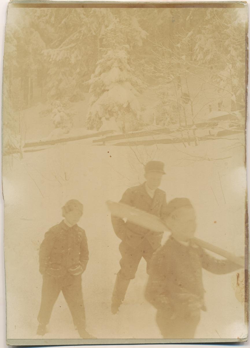 Tre gutter ute i snøen. En bærer en åre over skulderen.