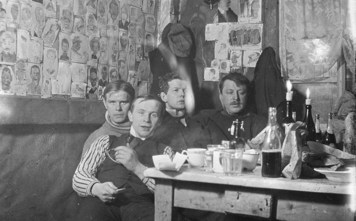 """Menn ved kjøkkenbord i hytte i Vardø. Veggen er dekket av karikaturtegninger. Bildetekst:""""I Birgerhy"""