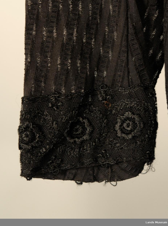 Kjole med blonder på armlinning, rundt hals, på bærestykke og nede på skjørt. Knapping bak til livet.