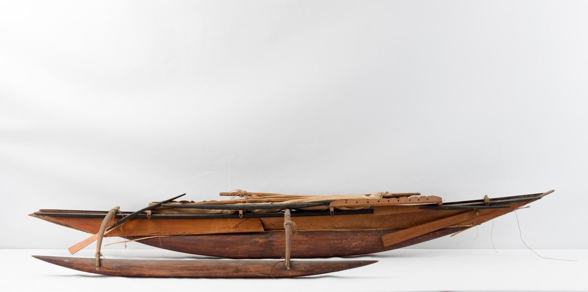 Modell av utriggerkano med seil og mast.
