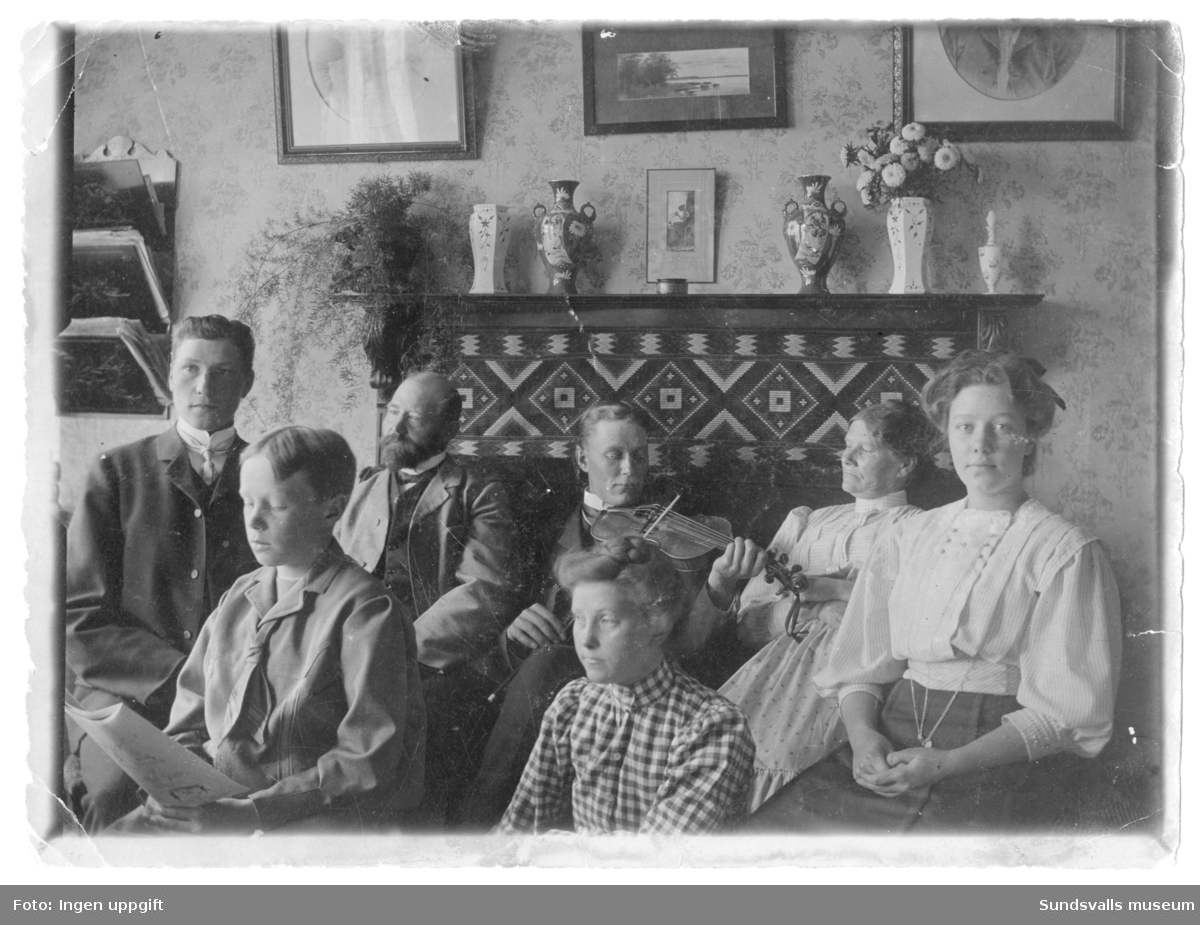 Familjen Lindvall samlad i bostaden. Bild 2: Trädgårdsmästare Edvard Lindvall sitter tredje från vänster och hans hustru Ida sitter andra från höger. Lindvalls handelsträdgård låg i sluttningen nedanför Norrliden. Intill trädgårdsanläggningen låg även privatbostaden. Handelsträdgården anlades redan på 1890-talets början av trädgårdsmästare Edvard Lindvall (1852-1914) och flyttades under 1960-talet till Alnö då nya E4-sträckningen drogs över den nedre delen av trädgårdsanläggningen.