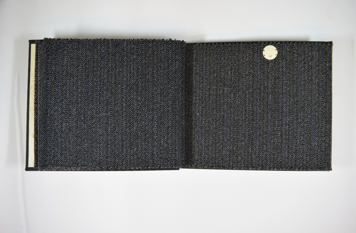 Prøvebok med 6 stoffprøver. Middels tykke stoff med fiskebensmønster og/eller striper. Stoffene ligger brettet dobbelt i boken slik at vranga dekkes. Stoffene er merket med en rund papirlapp, festet til stoffet med metallstift, hvor nummer er påført for hånd. Innskriften på innsiden av forsideomslaget indikerer at alle stoffene har kvalitetsnummer 128B.   Stoff nr.: 128B/1, 128B/2, 128B/3, 128B/4, 128B/5, 128B/6.