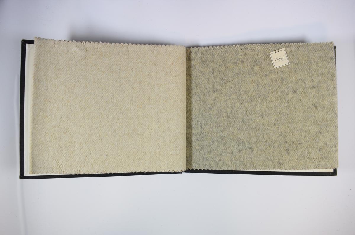 Prøvebok med 2 stoffprøver. Middels tykke tofargede stoff (det ene med hvit og beige, det andre med hvit og grå). Kyperbinding/diagonalvevd. Stoffene ligger brettet dobbelt slik at vranga dekkes. Stoffene er merket med en firkantet papirlapp, festet til stoffet med metallstift, hvor nummer er påført for hånd.   Stoff nr.: 100/1, 100/2.