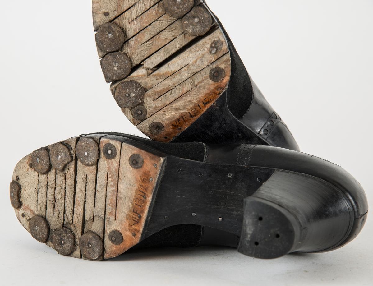Sko, A og B i skinn og svart fløyel. Snøresko med fem par hol, svart skolisse. Høg hæl, sole av gjennomskåren finer.  Dette er for å gjera den litt meir bøyeleg. Under solen er det spikra på 10 runde lerlappar. Skoa er laga under krigen.