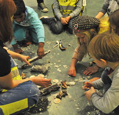 Barn sitter i sirkel, leker arkeologer, graver ut funn fra sandkasser.