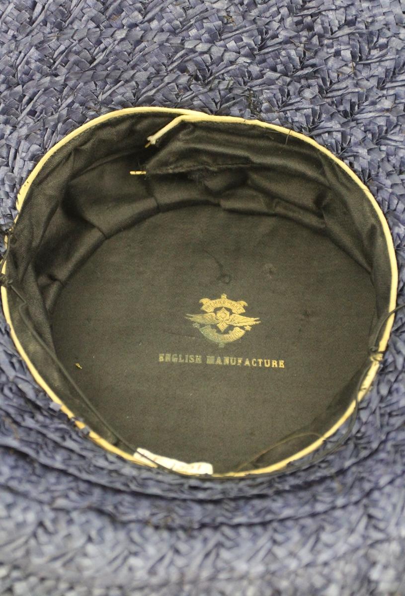 Stråhatt til dame. Bred brem krummet opp bak. Pullen sylindrisk, meget videre enn hodet og med flat topp bak. Oppå pullen en gren av 12 små hvite roser. Fra grenen og ned til bremmens ytterkant er der radiært lagt en rekke brede taftbånd på hattens venstre side. Det bakerste av disse båndene er ført rundt pullen og frem på høyre side av bremmen. På undersiden er bremmen mørkeblå, på oversiden er hatten lysere blå (dessuten nokså falmet). Sort satinfor.