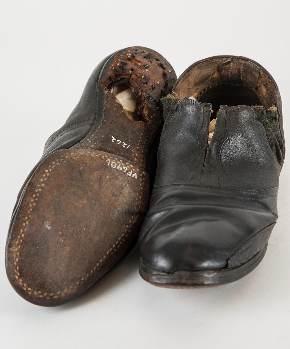 """Sko i brunt skinn, innsett """"strikk"""" i kvar side. Dekor. Oppklypt midt framme. Hælen er borte og det er stort hol under. Holet er sannsynlegvis laga ein gong for å få skoa på ei utstillingsdokke. Høgre sko.  Same sko som VFF 06485."""