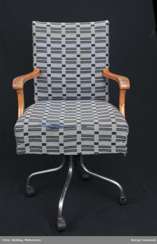 Svingbar skrivebordstol med armlener. Stoffet er festet med nagler. Møbelstoff. Setet er slitt. Hjul av plastikk.