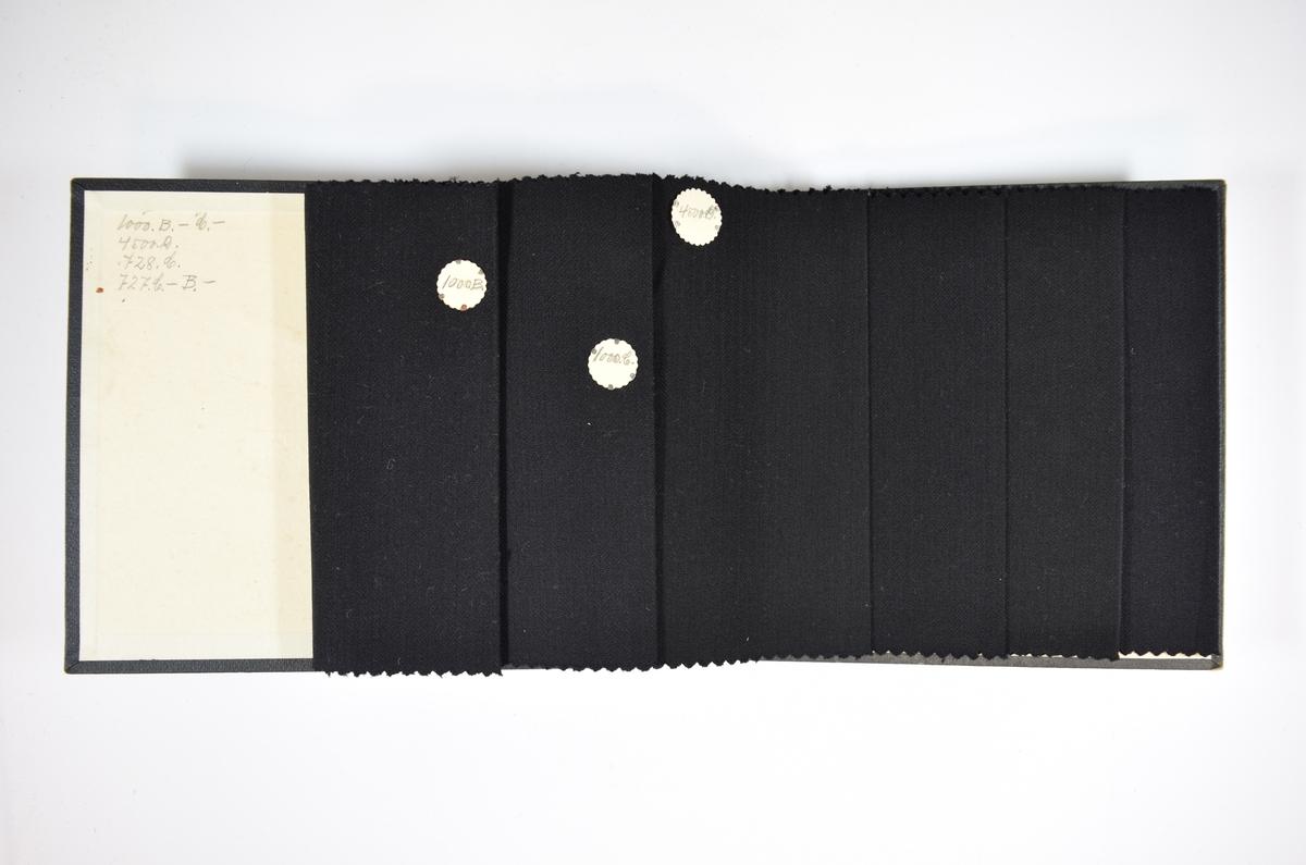 Prøvebok med 6 stoffprøver. Relativt tynne ensfargede mørkeblå stoff med fiskebensmønster i veven. Stoffene ligger brettet dobbelt slik at vranga skjules. Stoffene er merket med en rund papirlapp, festet til stoffet med metallstifter, hvor nummer er påført for hånd.    Stoff nr.: 1000B, 1000G, 4500D, 728G, 727G, 727B.