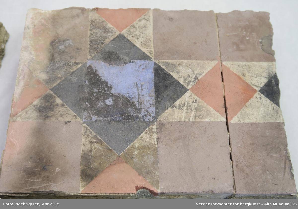 Bruddstykker av gulvfliser med dekor av geometriske fargefelter med tre- og firkanter. Flisene er støpt fast i sement.