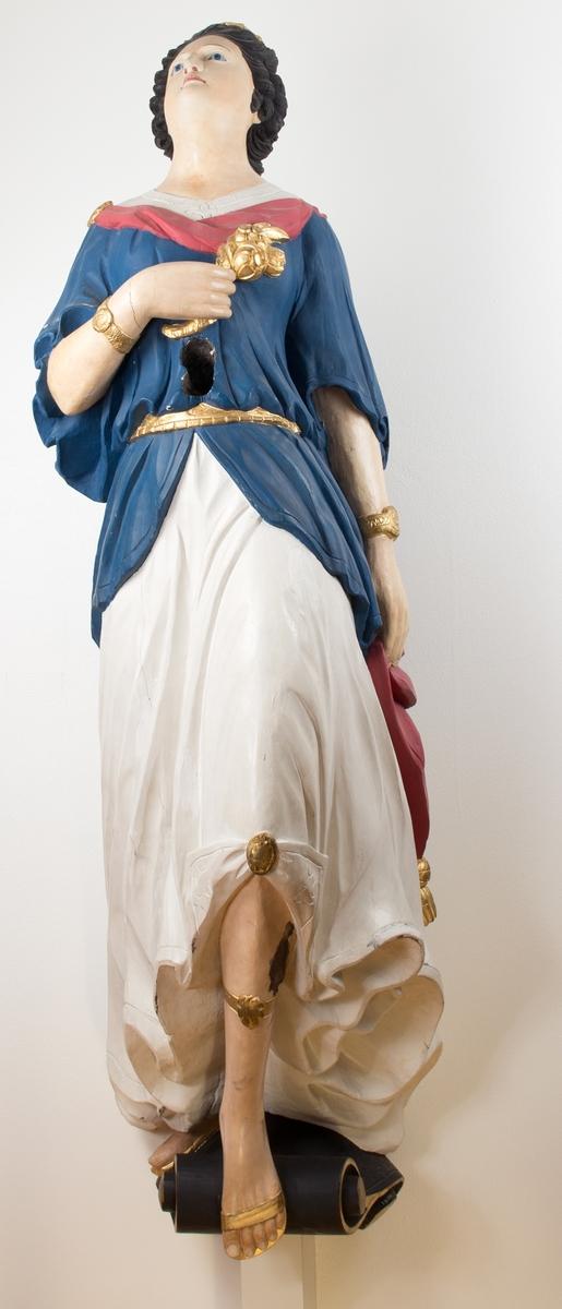 Kvinnefigur med oppsatt hår. Kjolen er drapert rundt bena, leggene er bare. Over kjolen bærer hun en jakke, som er festet med et belte. Figuren bærer armbånd på begge armene, og har et bånd rundt den fremre leggen. Føttene har lette sandaler, og i hånden bærer hun en blomsterbukett. Figuren står på en liten sokkel.