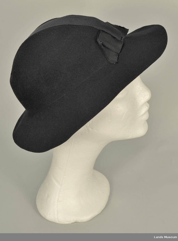 Ullfilt. Avskåret hattebrem. Ripsbånd tvers over (frå panne til nakke) pullen. Sløyfe foran.