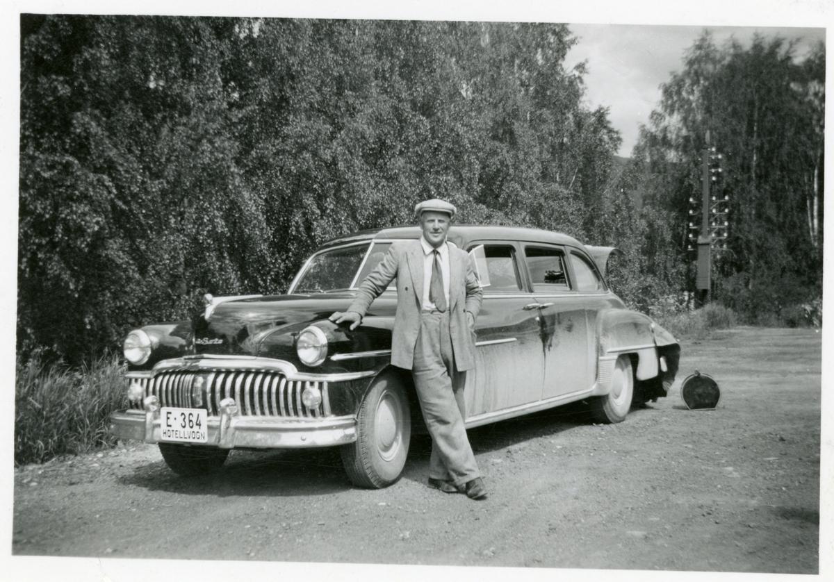 Olaf Bruhallen med hotellgjester i ihotellbilen. Merket er Desoto.