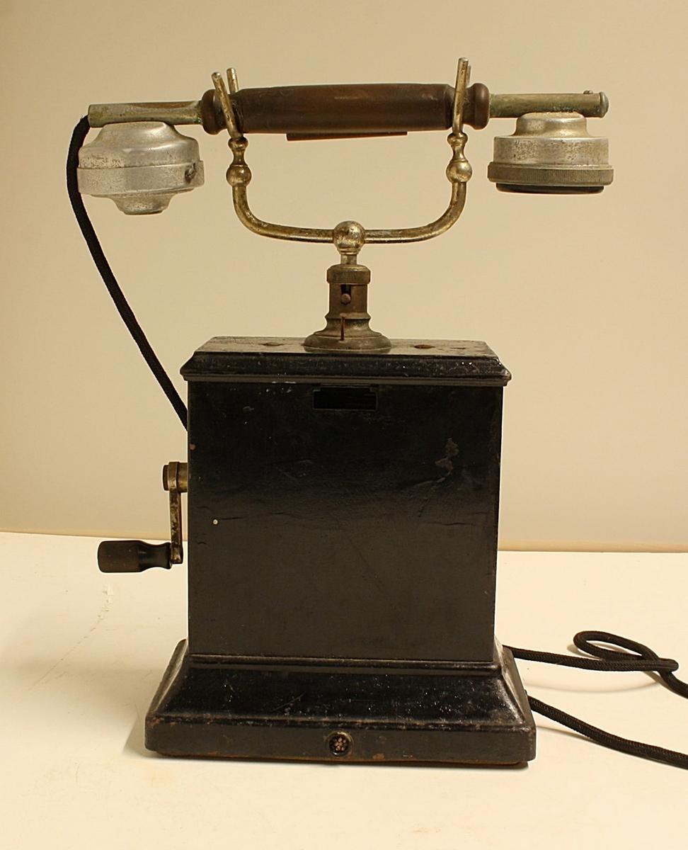 Har toppmontert gaffel med mikrotelefon. Sveiveinduktor. Høretelefonen er av elektromagnetisk type. Trakten er hel og apparatet ellers komplett.
