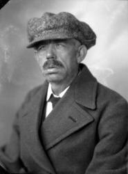 Ateljébild på en man i blazer och keps. Beställare till bild