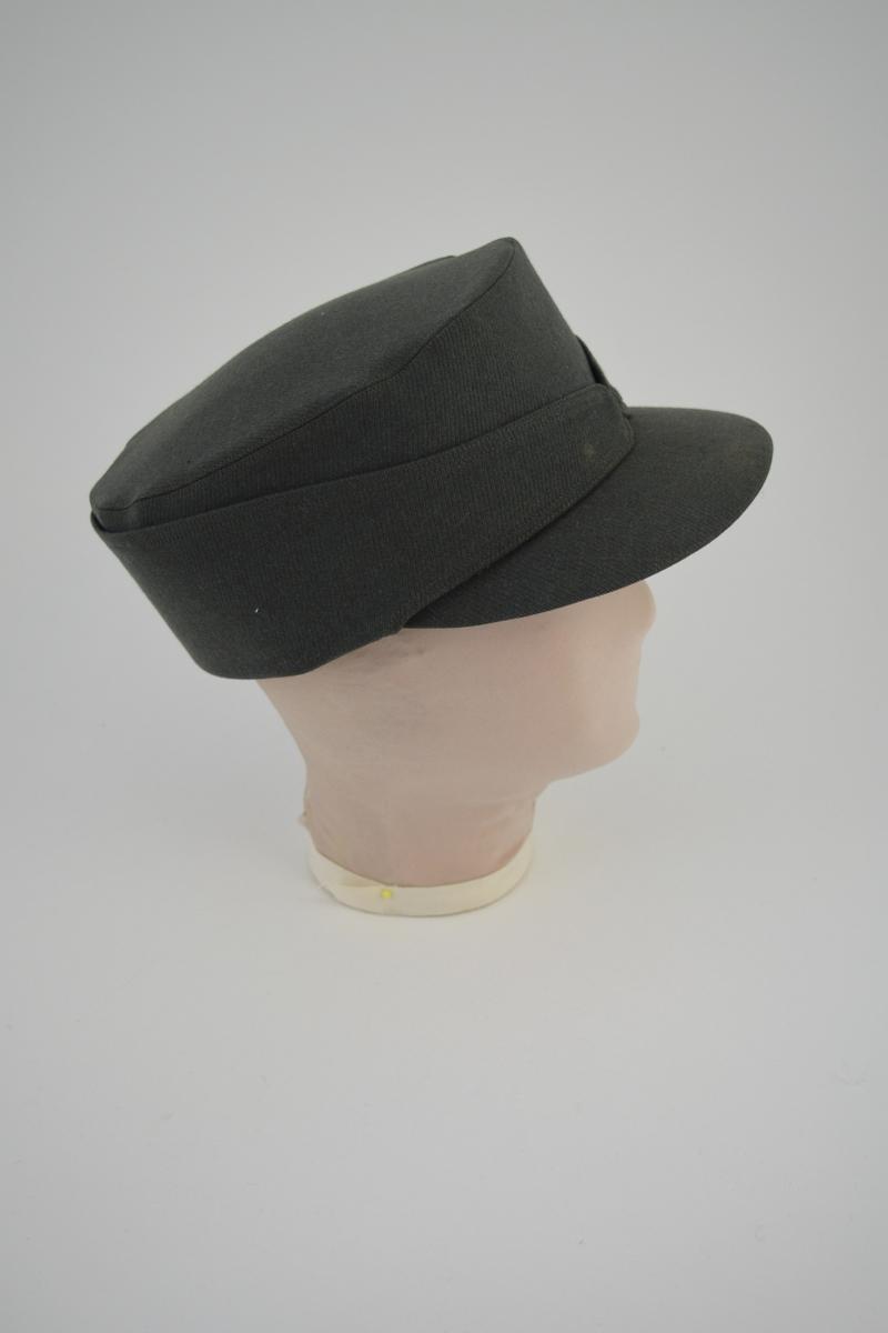 Form: Oval, hodeformet, bred avstivet kant, plan oval hattepull,  stofftrukket. Bred buet, stofftrukket skygge. Hattepull innvendig vattert. På innsiden et nedfellbart nakkestykke/ørevarmere.   Et nakkestykke er brettet opp bak og avsluttes med to spisser som er lagt kant i kant i luens midtpunkt foran.
